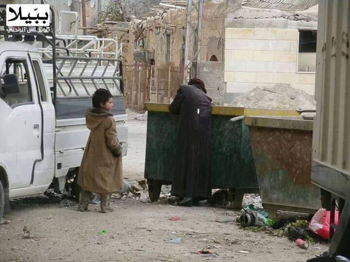 امرأة سورية تبحث لطفلتها عن الطعام في حاويات القمامة